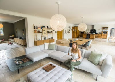 L-shape sofa and poof showing stunning lampshade and dining area in background. NW3 Interiors transformed our Beaconsfield Home. Click to view on the NW3 interior design portfolio.