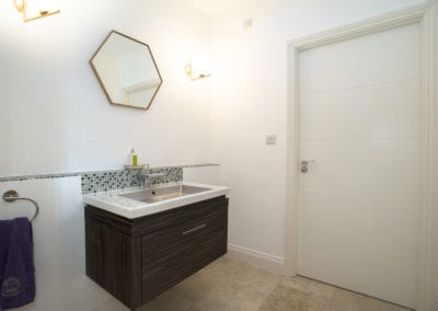 Bathroom with hexagonal mirror. NW3 Interiors transformed our Beaconsfield Home. Click to view on the NW3 interior design portfolio.