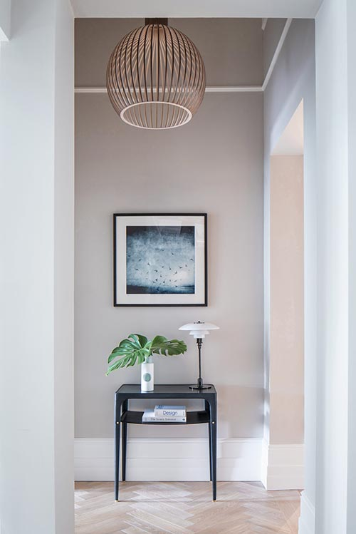 Hallway image with table, plant, lamp and art hanging. Put together by NW3 Interiors, North London Interior Designers.