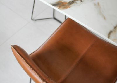 Detailed shot of a leather chair and marble top in a kitchen